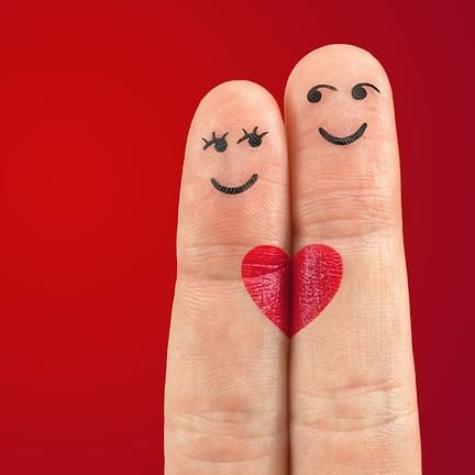 Two fingers with faces drawn on them and a heart
