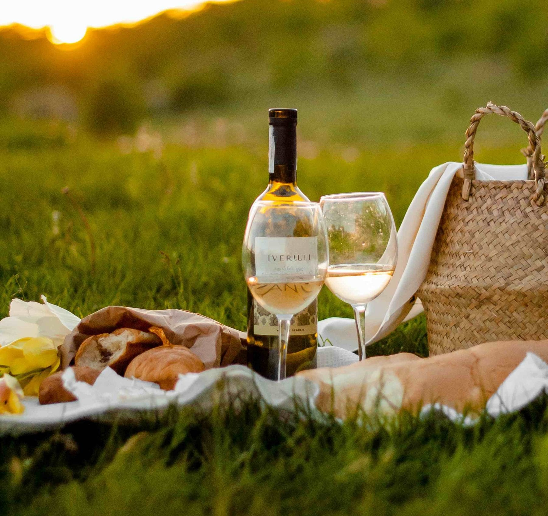 wine and cheeses on a picnic setting in the grass