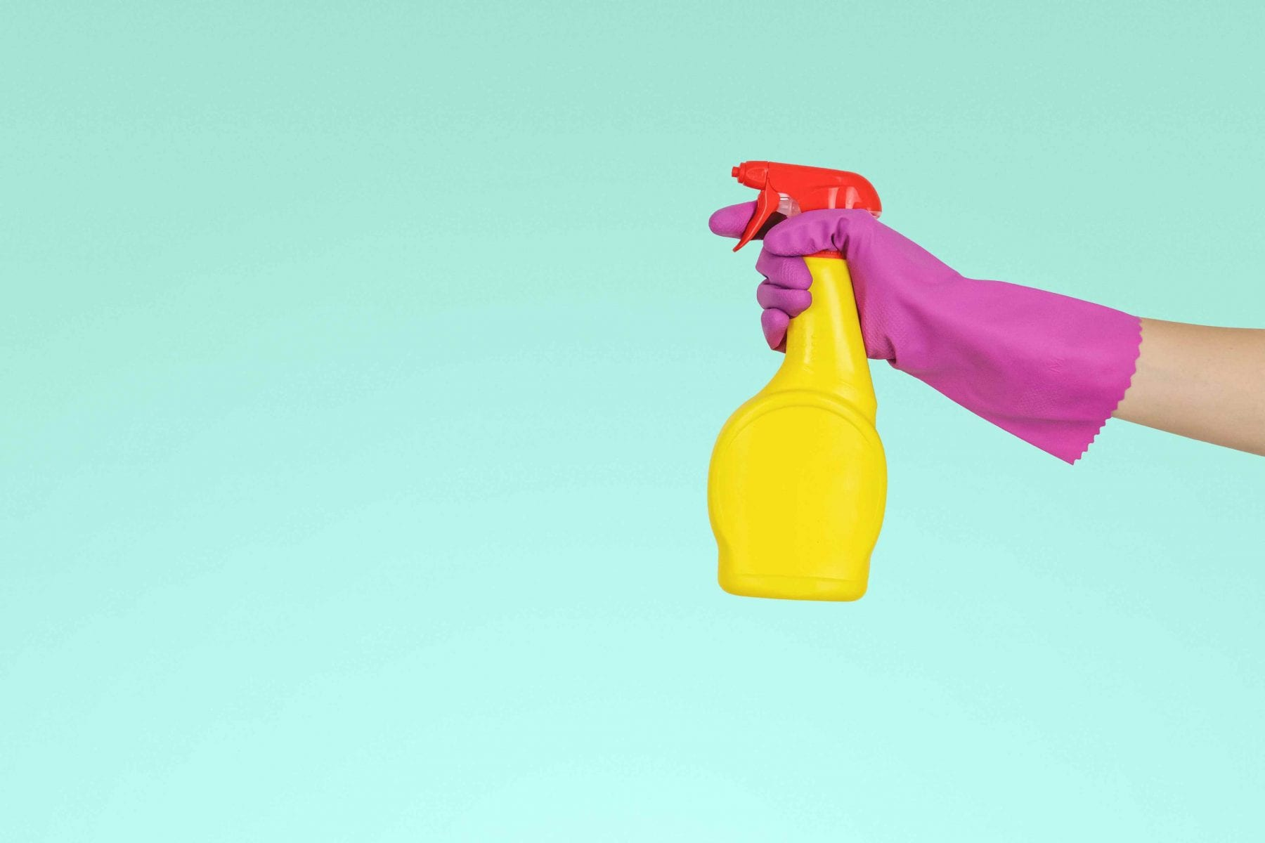 person wearing pink glove holding cleaning bottle