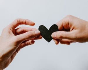 Two different people's hands holding a black paper cut out heart