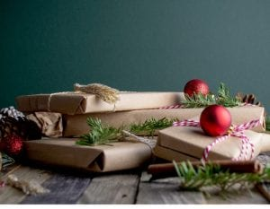 Multiple xmas gifts in brown paper wrap with red baubles on top and green decoration